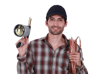 Plumber with blow-torch and copper pipe