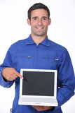 Manual worker pointing to laptop