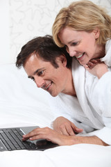 Couple on laptop in dressing gown.