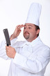 Professional chef checking his image in a knife