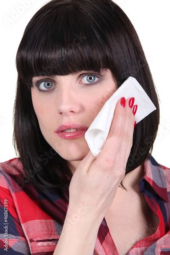Woman wiping her face with a tissue