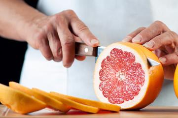 Horizontal shot of female hands cutting a grapefruit, close-up