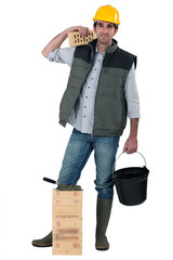 Bricklayer carrying bucket