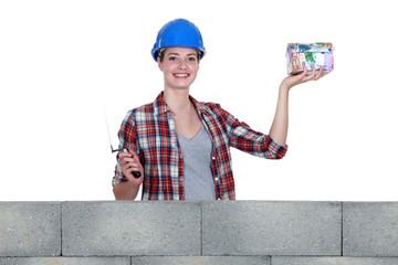 Female in mason clothing holding a house-shaped piggy bank