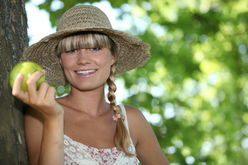 Woman in straw hat holding apple