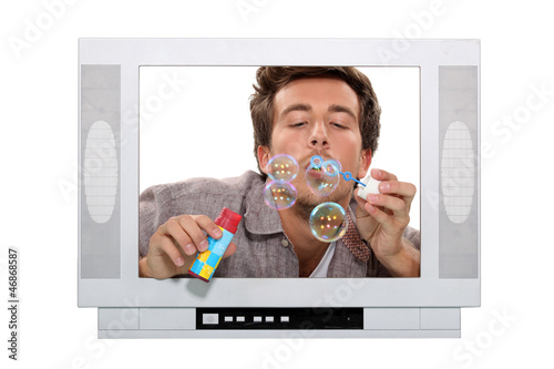 Man blowing bubbles inside television