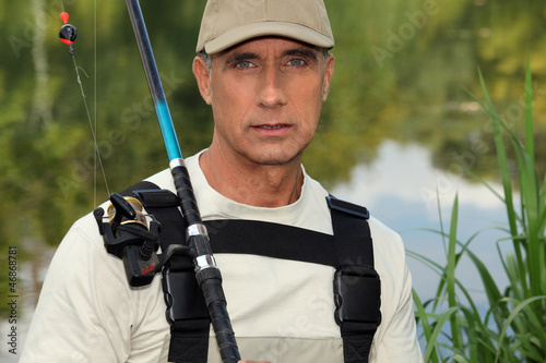handsome middle-aged fisherman by riverside