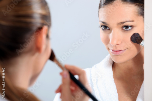 Woman applying blusher in a mirror