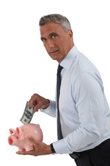 handsome mature banker and piggy bank
