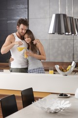 Young couple having orange juice in the morning