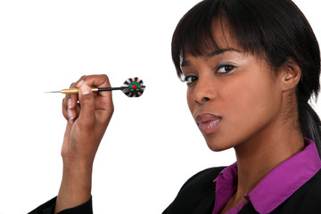 A businesswoman playing darts.