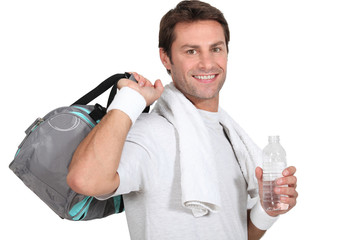 A sportsman smiling at us and holding bag and water