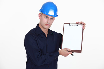 Manual worker stood with clip-board and pen
