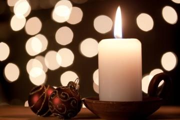Kerze mit Weihnachtsbaumkugeln und Lichterkette
