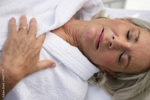 Elderly lady wearing bathrobe relaxing