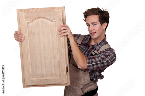 A carpenter holding a closet door.