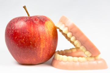 Zahnprothese mit Apfel