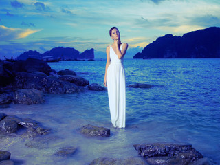 Lady in white dress on seashore