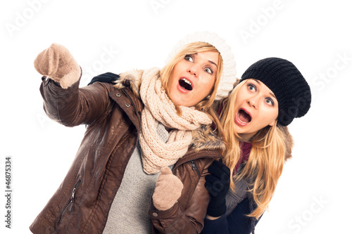 Shocked women in winter clothes pointing