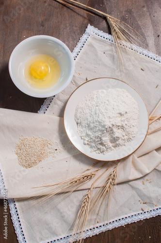 Raw egg in plate, flour, til, wheat on light tablecloth