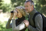 A mature couple,  woman looking through a pair of binoculars
