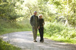 A mature couple walking along a country path holding hands