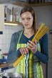Frau kocht Spaghetti in der Küche