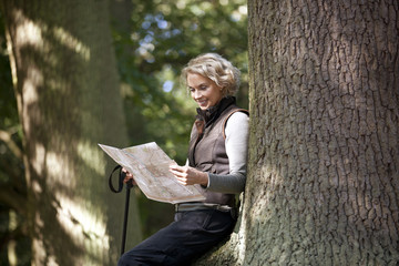 A mature woman resting on a tree, looking at a map, close up
