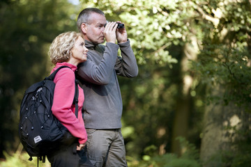 A mature couple in the countryside looking through binoculars