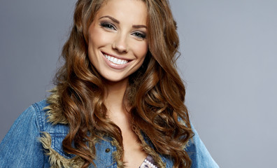 young gorgeous brunette model in jeans jacket, studio shot