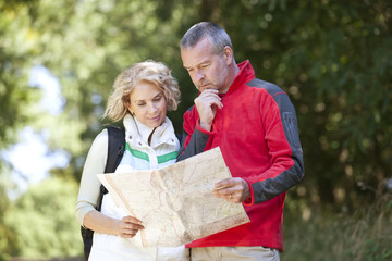 A couple walking in the countryside looking at a map, close up