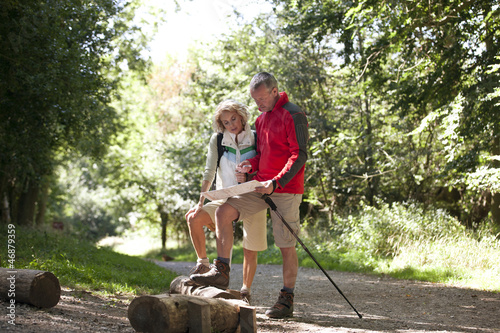 A mature couple standing on a country path, looking at a map