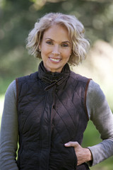 A portrait of a mature woman outdoors, smiling