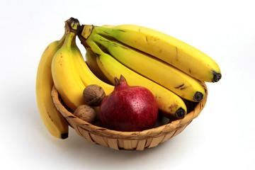 cesto di frutta con banane,noci e melograno
