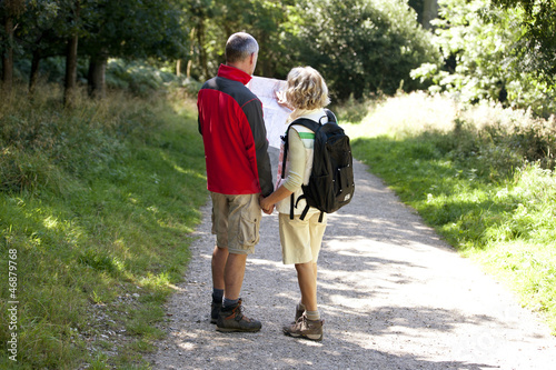 A mature couple walking in the countryside, holding a map