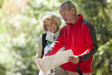 A couple walking in the countryside, looking at a map