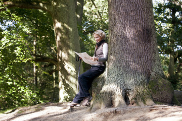 A mature woman resting on a tree, looking at a map