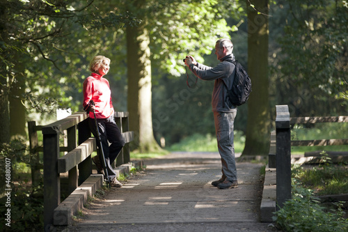 A man taking a photograph of his partner outdoors