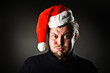 Portrait of man blowing out cheeks and wearing Santa hat