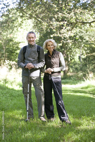 A mature couple standing in the countryside together