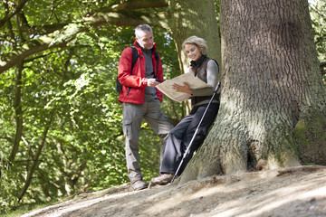 A mature couple standing in woodland looking at a map