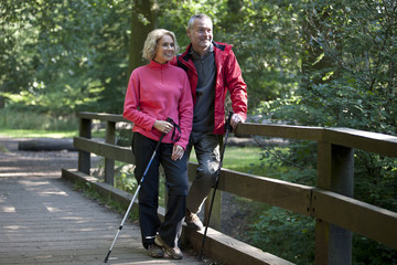 A mature couple standing on a footbridge in the countryside