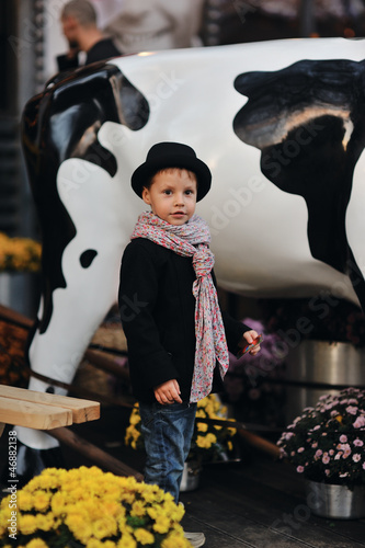 child in a black coat and hat near the cows