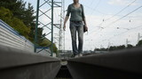 Young woman walking on the rail siding
