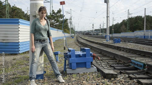 Young woman standing at the pillar on the railroad