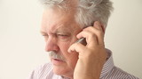 angry senior man on mobile phone