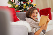 Happy woman with book near Christmas tree