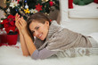 Smiling woman laying near Christmas tree