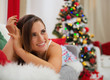 Happy woman laying on couch in front of Christmas tree