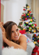 Happy woman laying on sofa in front of Christmas tree